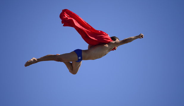 Czech Michal Navratil dives for a joke as superman after of the men's high diving final competition at the FINA World Championships in Moll de la Fusta port in Barcelona on July 31, 2013