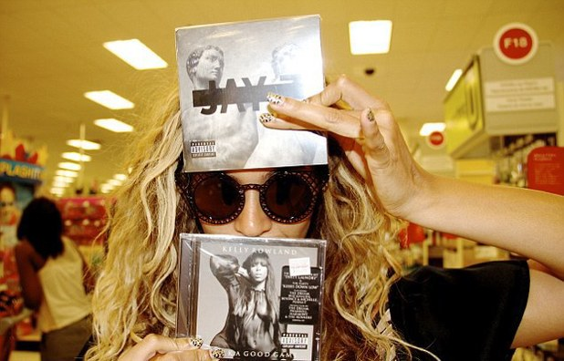 Beyoncé poses with albums by Jay Z and Kelly Rowland