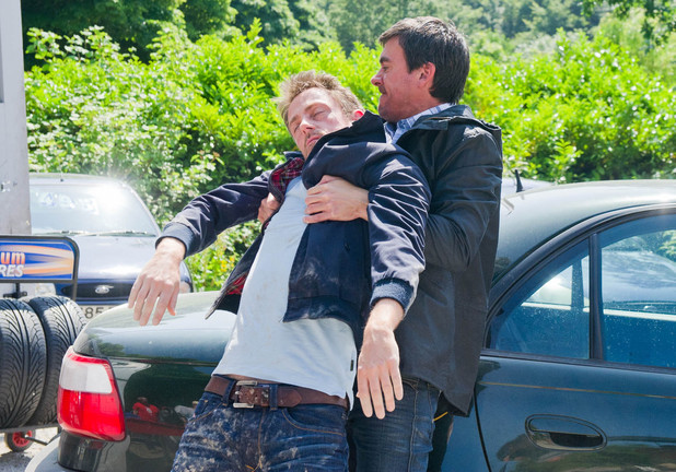 Cameron is unconscious as Cain bundles him into his car.