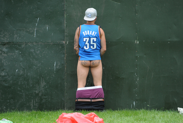 A festival goer urinates by the Futures stage during day one of the V Festival at Weston Park in Weston-under-Lizard.