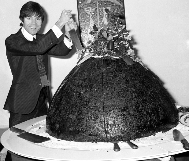 PA Photo 4/12/68 Cliff Richard cuts through the World's Largest Christmas Pudding at the Carlton Tower in London to be distributed to the Mental Health Trust for patients and hospitals throughout the country