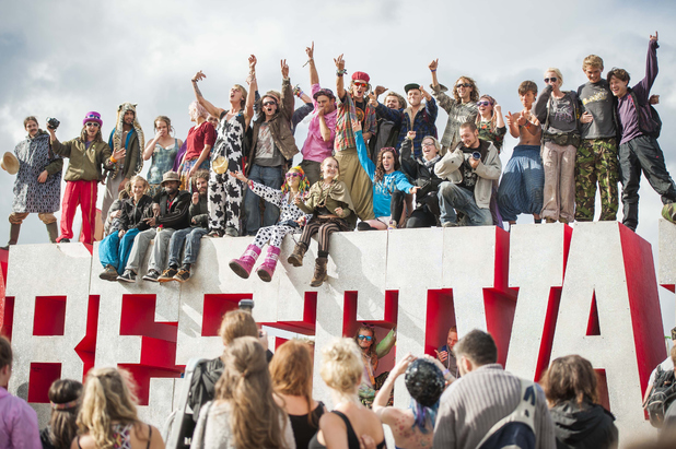 Festival goers climb the Bestival sign
