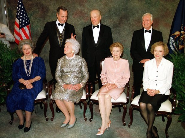** FILE ** In a file photo former President George Bush makes rabbit ears behind his wife, Barbara, as former presidents and first ladies wait for the official portrait during a gala Wednesday night, April 16, 1997, in Grand Rapids, Mich., in honor of the rededication of the Ford Museum. Front row from left are Lady Bird Johnson, Barbara Bush, Betty Ford, and Rosalynn Carter. Back row from left are former Presidents George Bush, Gerald Ford, and Jimmy Carter. Former first lady Betty Ford said Tuesday Dec. 26, 2006, that President Gerald Ford has died.(AP Photo/Carlos Osorio)