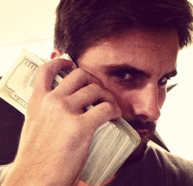 Scott Disick using money as a phone