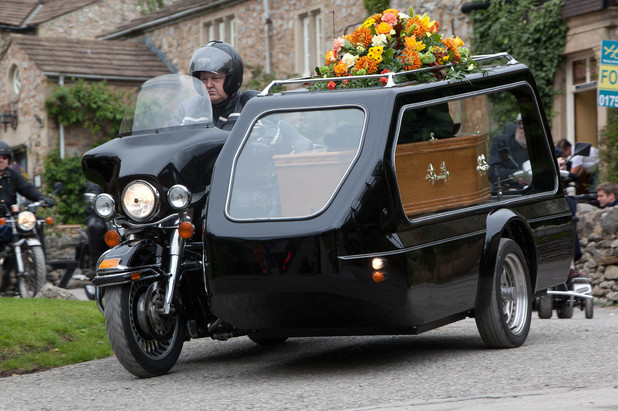 The procession of motorbikes arrives with Alan's coffin.