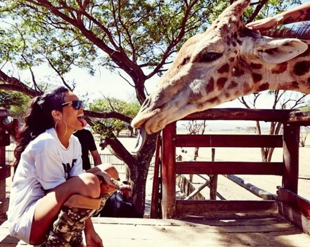 Rihanna sticks her tongue out at a giraffe