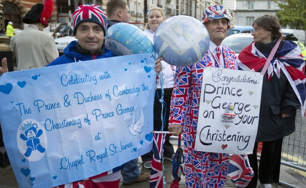 Royal wellwishers gather and display their home made placards and greetings to the media as they await the christening of Prince George