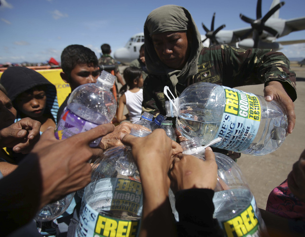 A Filipino trooper distributes water to survivors of Typhoon Haiyan
