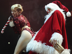 Miley Cyrus twerks with a Santa Claus dancer during the KIIS-FM Jingle Ball concert