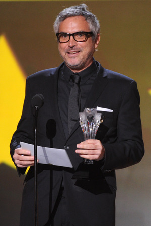 "Alfonso Cuaron accepts the award for best actress in an action movie for ""Gravity"" at the 19th annual Critics' Choice Movie Awards"