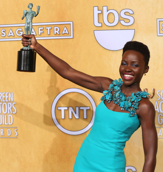 "Lupita Nyong'o poses with the award for outstanding performance by a female actor in a supporting role for ""12 Years a Slave"""