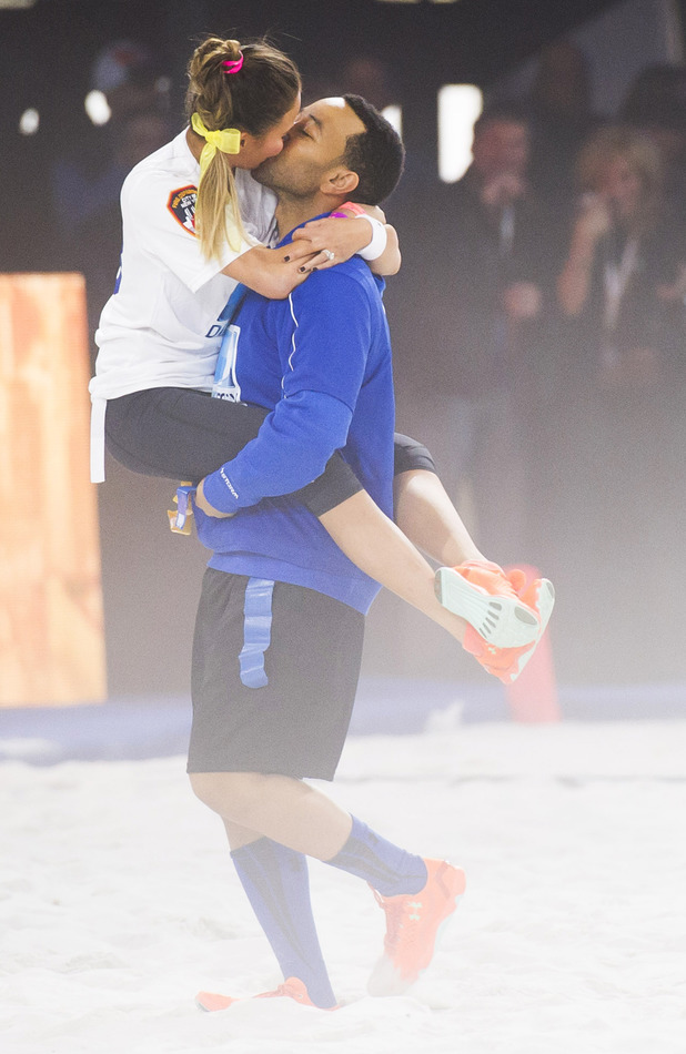 Chrissy Teigen and John Legend kiss on the field during DIRECTV's 8th annual Celebrity Beach Bowl