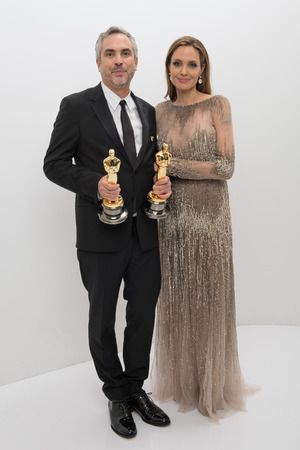 "A.M.P.A.S. After winning the categories for Achievement in Film Editing and Achievement in Directing for work on ""Gravity"", Alfonso Cuaron poses backstage with his Oscars® and presenter Angelina Jolie 2 Mar 2014 86th Annual Academy Awards Oscars, Portraits, Los Angeles, America - 02 Mar 2014"