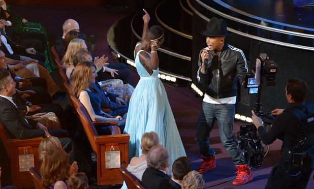 "Lupita Nyong'o, left, dances along with Pharrell Williams during his performance of ""Happy"""