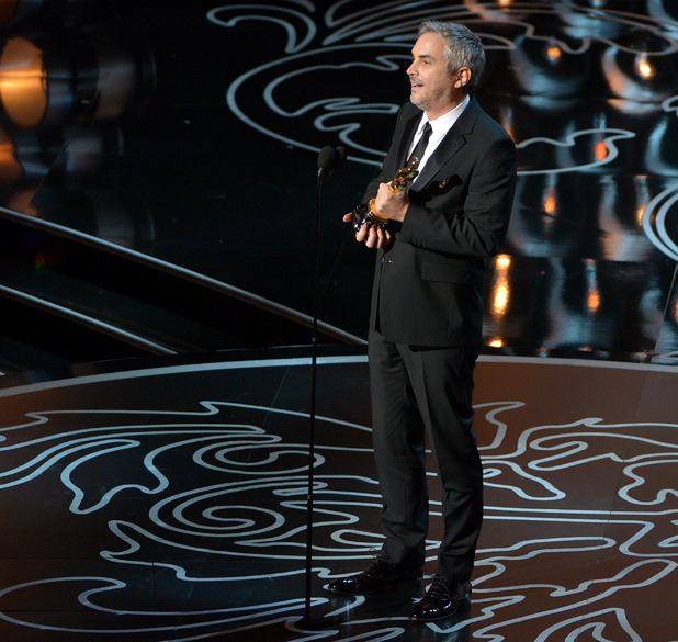 "Alfonso Cuaron accepts the award for best director of the year for ""Gravity"" during the Oscars"
