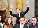 Sherlock star has fun behind Bono at the Academy Awards.