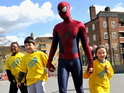 Andrew Garfield puts on the iconic Lycra suit to visit charity Kids' City.