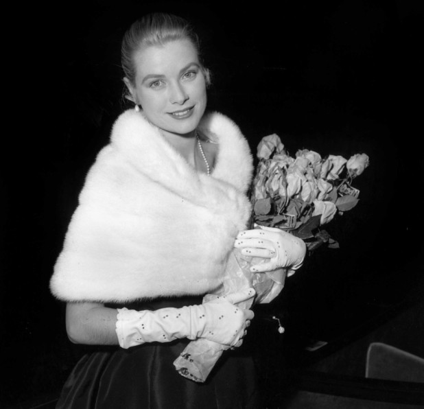 American actress Grace Kelly wearing a fur wrap and carrying a bouquet of roses at the International Cannes Film Festival, 6th May 1955. (Photo by RDA/Hulton Archive/Getty Images)