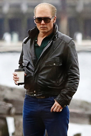 Boston, MA - Johnny Depp gets into character as famed mobster James Whitey Bulger on the set of Black Mass. Cameras rolled as the 50-year-old actor and co-stars filmed a mob hit on location in Boston. Johnny stood by calmly as a character was gunned down near a port. Depp warmed up with a hot beverage in between takes as he chatted with the cast and crew. Johnny and his co-stars shared a laugh and some hugs after the scene was complete.
