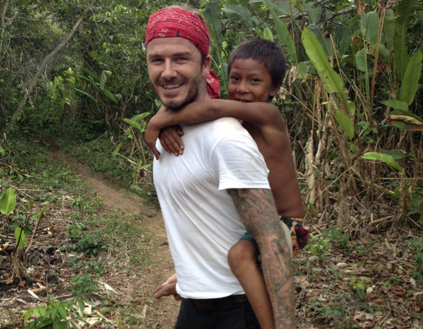 David Beckham Into The Unknown: David Beckham in the Amazon Rainforest with a child from local tribe