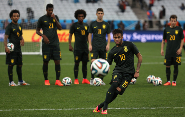 Neymar of Brazil shoots as his teammates look on during a Brazil training session ahead of the 2014 FIFA World Cup Brazil opening match against Croatia