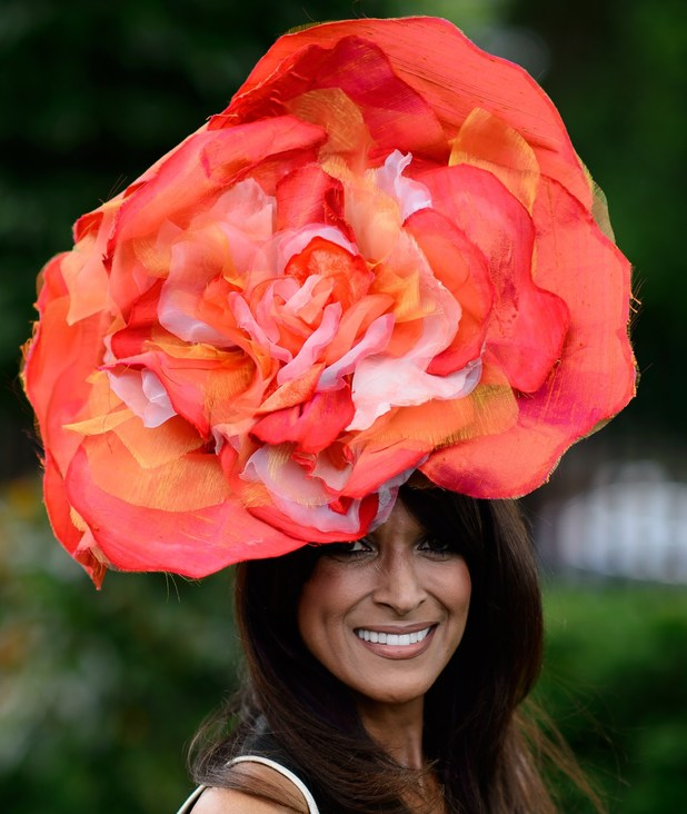 A racegoer poses for photographers on the second day of the Royal Ascot horse racing meet, in Berkshire, west of London, on June 18, 2014. Horse racing has been held at the famous Berkshire course since 1711 and tradition is a hallmark of the meeting. Top hats and tails remain compulsory in parts of the course while a daily procession of horse-drawn carriages brings the Queen to the course. AFP PHOTO / LEON NEAL (Photo credit should read LEON NEAL/AFP/Getty Images)