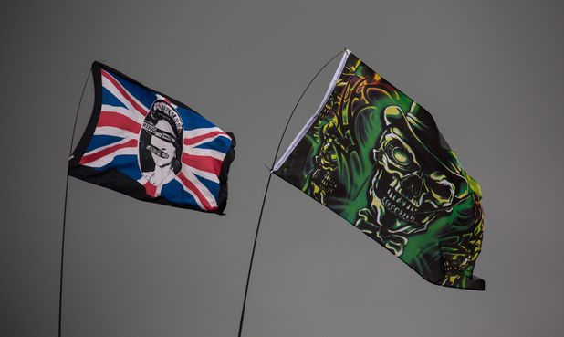 Festival flags blow in the wind against an ominous backdrop at Glastonbury Festival 2014