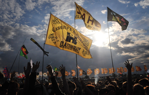 Flags fly in the air as the sun sets on Glastonbury day 2