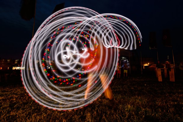 A girl uses a glowing hula hoop at Glastonbury Festival 2014