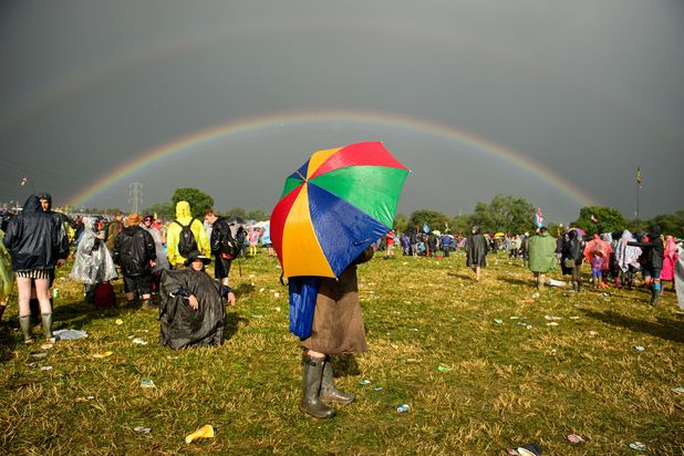 Following a very heavy rainstorm, a double rainbow appears in the sky above the Glastonbury site