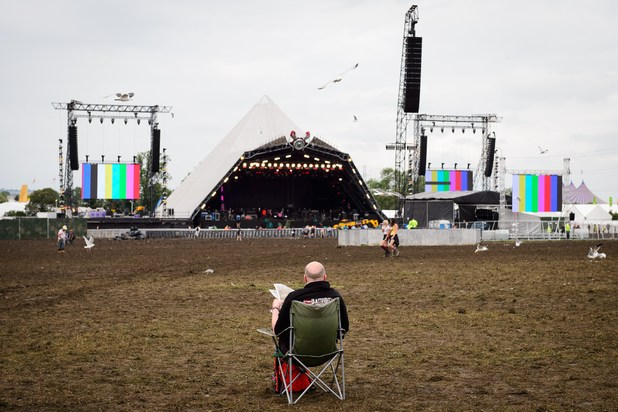 A man reads his Sunday newspaper as revellers wake on the last day of the Glastonbury Festival