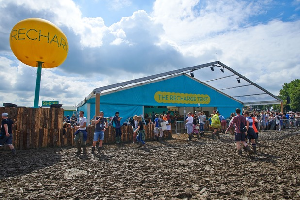 Festival goers queue to charge their phones outside the EE Recharge Tent
