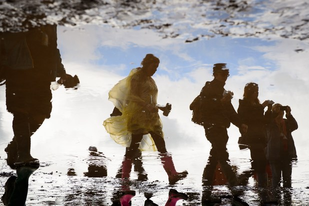 Revellers are reflected in a puddle near to the Pyramid Stage during Glastonbury 2014