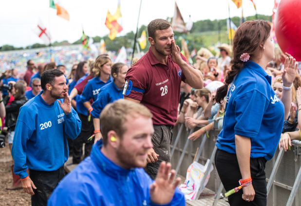 The security team line dance as Dolly Parton performs on the Pyramid Stage