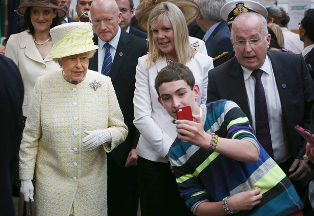 A teenager tries to take a selfie infront of Queen Elizabeth II during a walk around St. Georges Market in Belfast