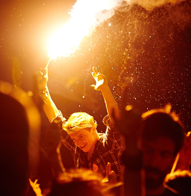 A festival goer enjoys the atmosphere holding a flare in the crowd during Metallica's performance on the Pyramid Stage