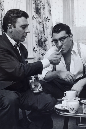 Crime. London, England. Circa 1960's. The Kray Twins. Reg (left) and Ronnie Kray smoking a cigarette and drinking tea. Caption:Crime, London, England, Circa 1960's, The Kray Twins, Reg (left) and Ronnie Kray smoking a cigarette and drinking tea (Photo by Popperfoto/Getty Images)