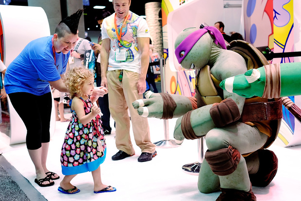 Two year old Ellie Campbell gets a high-five from the Teenage Mutant Ninja Turtle character Donatello during the 45th annual San Diego Comic-Con