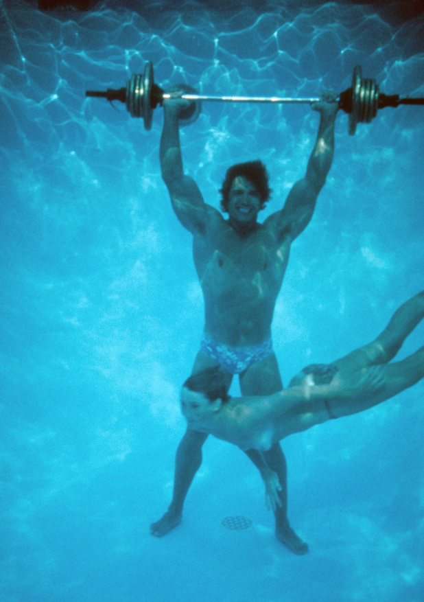 LOS ANGELES - CIRCA 1977: Austrian Bodybuilder Arnold Schwarzenegger lifts a barbell at the bottom of a pool as a topless girl swims by circa 1977 in Los Angeles, California. (Photo by Michael Ochs Archives/Getty Images)