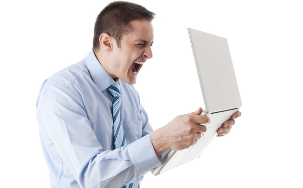 An angry man holds a laptop