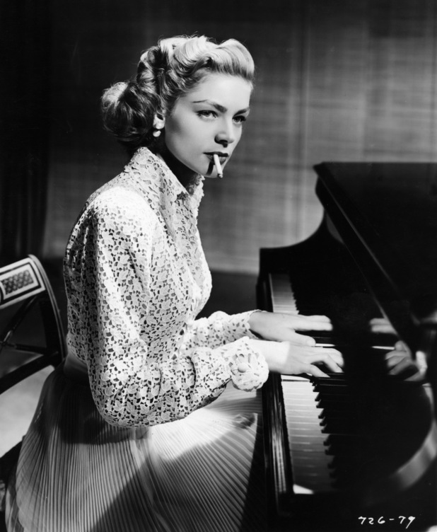 American actress Lauren Bacall (born Betty Joan Perske) smokes as she plays piano in a scene from the film 'Young Man with a Horn' (directed by Michael Curtiz), California, 1950. (Photo by Metronome/Getty Images)