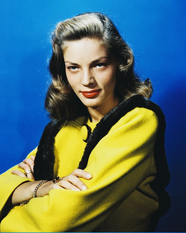 Lauren Bacall, US actress, wearing a yellow jacket with black trim in a studio portrait, against a blue background, circa 1945. (Photo by Silver Screen Collection/Getty Images)