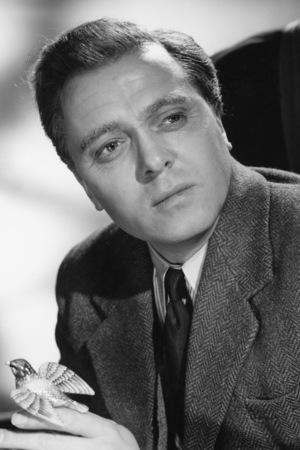 English actor and director Richard Attenborough holding a small model of a bird in a promotional portrait for 'Jet Storm', directed by Cy Endfield, 1959.