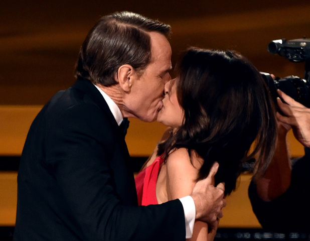 Julia Louis-Dreyfus wins Outstanding Lead Actress in a Comedy Series for Veep and kisses actor Bryan Cranston onstage at the 66th Annual Primetime Emmy Awards