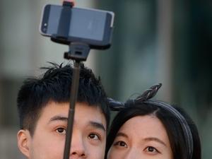 A couple on Korea uses a selfie sti