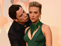 Travolta creeps up on Johansson for kiss