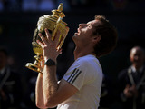 Andy Murray lifts the trophy after the mens singles final against Novak Djokovic on Centre Court during Wimbledon 2013