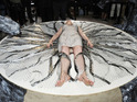 Gwendoline Christie layng on the catwalk during teh Iris Van Herpen show at Paris Fashion Week